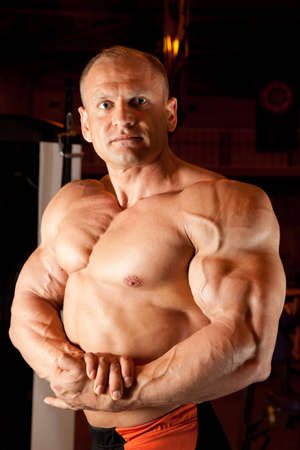 bodybuilder demonstrates his muscles photo