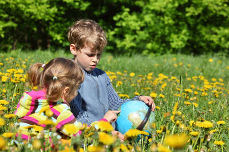 Two children with globe sit on meadow among blossoming dandelions photo