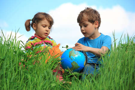 person outside: girl and boy with globe on meadow