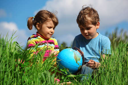 girl and boy with globe on meadow Stock Photo - 7838781