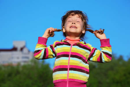 happy girl holds plaits and has closed eyes against sky Stock Photo - 7831552
