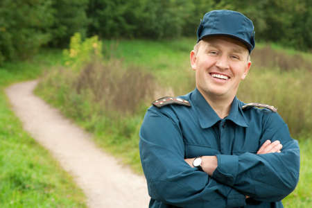 rescue service: smiling officer of rescue service standing on footpath outdoors Stock Photo