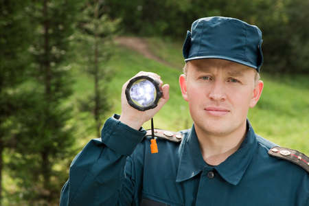 rescue service: officer of rescue service looking for something with flashlight