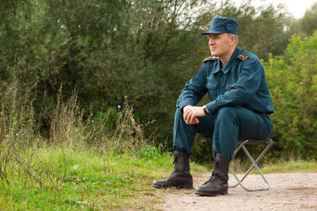 military man: military man sitting on the camp-chair outdoors