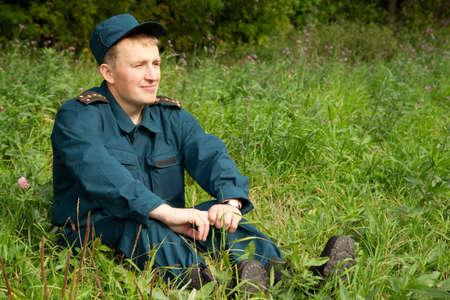 military man: military man sitting in green field