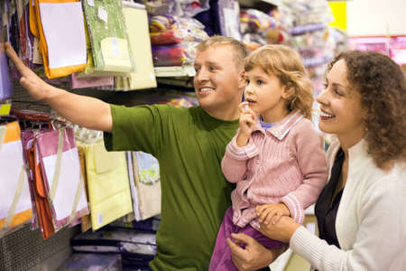 furniture store: family with little girl buy bedding in supermarket  Stock Photo