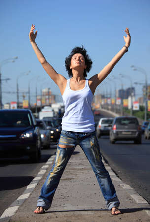 girl stands on middle of road with rised hands photo