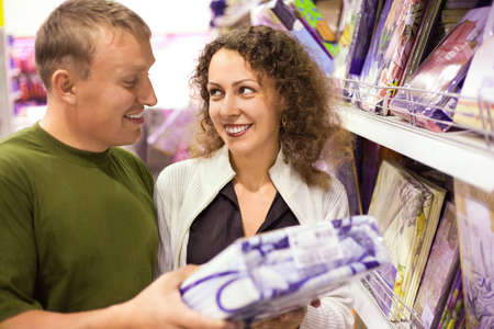 furniture store: Smiling young man and woman buying bedding in supermarket, looking each other