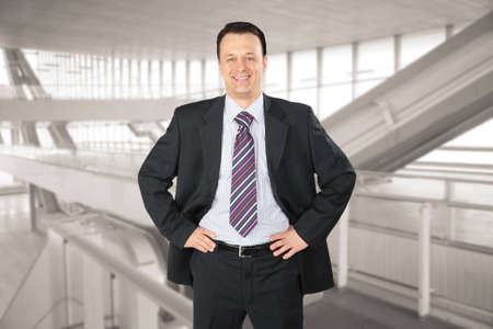smiling businessman in glass hall photo