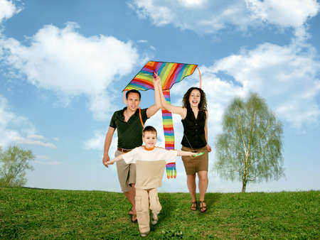 father, mother and child on grass with kite, collage photo