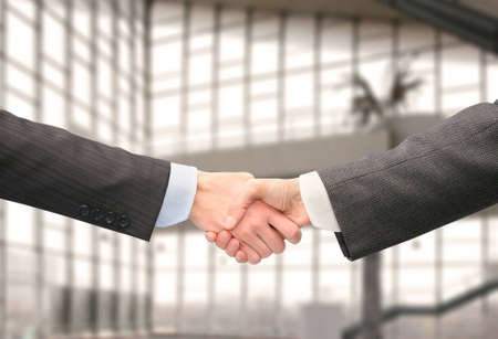 partnership security: shaking hands with wrists in hall of business center