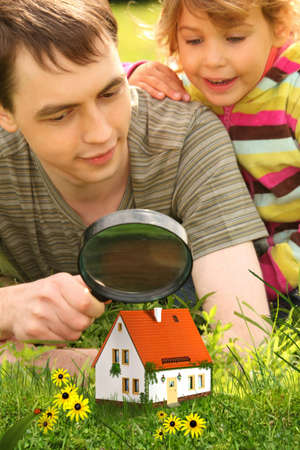 father with little girl looking on small house through magnifier collage photo