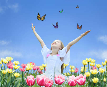 little girl in tulips with hands up and butterfly collage Stock Photo
