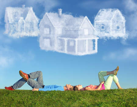 lying couple on grass and dream three cloud houses collage Stock Photo