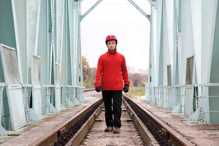blindly: trabajador hombre ciegamente en un casco se encuentra en el puente de rieles Foto de archivo
