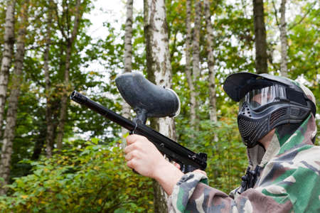paintball player shoots aside in forest photo