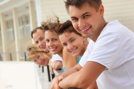 Five smiling friends on balcony photo