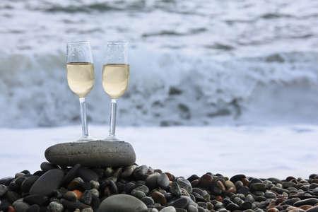 coastline: two glasses of wine on stony beach