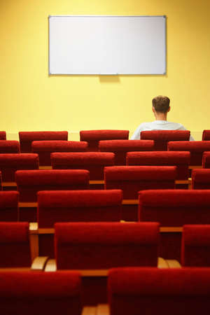 empty conference hall. rows of a chairs. focus on a first row. one man sitting in chair photo