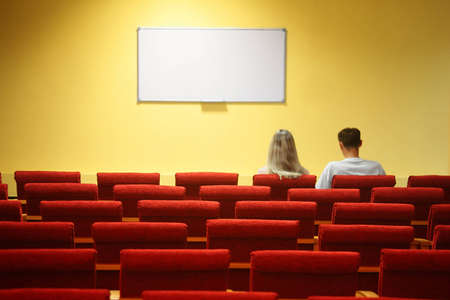 void: empty conference hall. rows of a chairs. focus on a third row. man and woman sitting in chairs Stock Photo