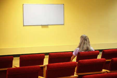 void: woman sitting in a chair in a first row of empty presentation hall. screen in out of focus. focus on a woman.
