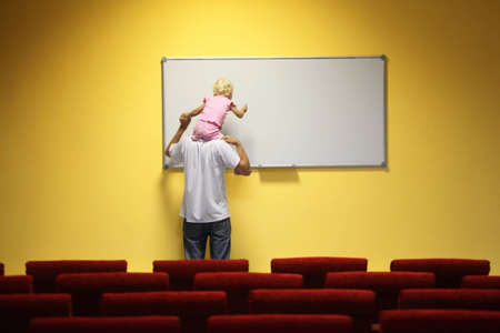 father and little girl in empty presentation hall. little girl is sitting on a father's neck. chair in out of focus. Stock Photo - 8974299