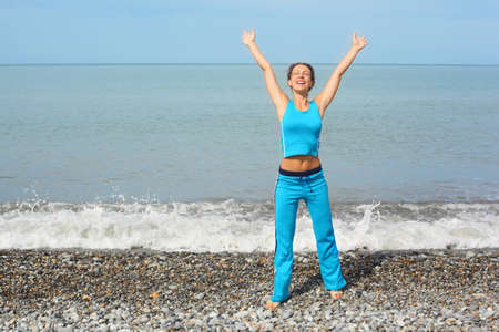 joyful woman wearing sporty clothers with raised hands on sea coast photo