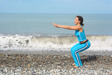 joyful woman wearing sporty clothers is making exercise on sea coast. she is squating. Stock Photo - 9110424