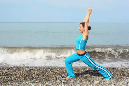 woman wearing sporty clothers is making exercise on sea coast and looking away photo