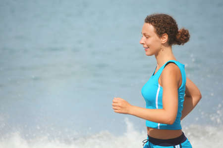 joyful woman wearing sporty clothers is running. sea in out of focus. photo