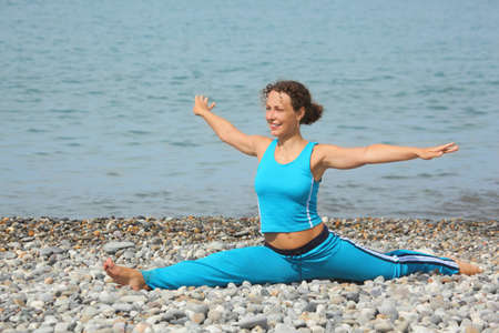 joyful woman wearing sporty clothers is smiling and stretching on sea coast. photo