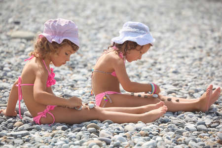 two little girls is playing with pebble stones. focus on little girl in a left side of image. photo