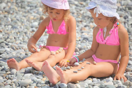 two little girls is playing with pebble stones. focus on girl with white panama hat on her head. photo