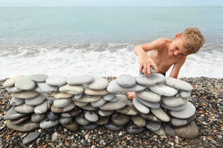 building foundation: little boy is building construction of many pebbles on a sea coast near water.