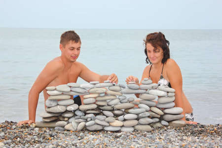 man and woman is building construction of pebbles near water. Stock Photo - 9112440
