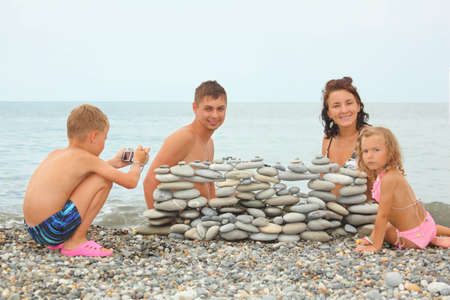 photocamera: family with two children near construction of pebbles. little boy with photocamera. Stock Photo
