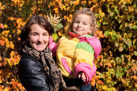 Mother hold daughter on hands on walk in autumnal park Stock Photo - 9113409