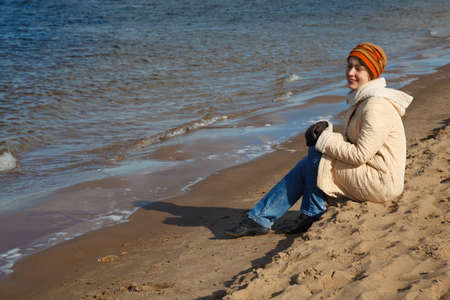 Girl sits on beach, an autumn sunny day. In cap, coat, jeans and sports shoes. photo