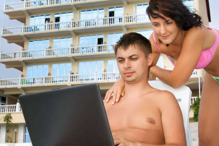 pretty woman and young man reclining on chaise lounges on beach near hotel, man looking in laptop screen photo