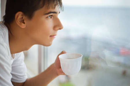 man drinking coffee: teenager boy with cup in hand looking out of window in morning, focus on cup