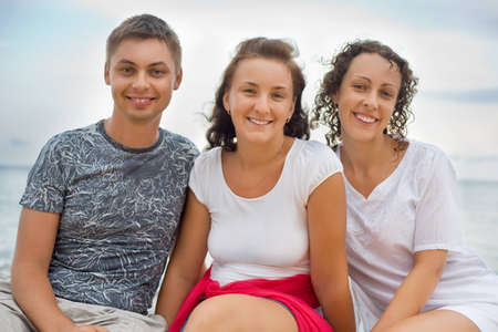 Smiling man and two young  beautiful women sitting on beach photo