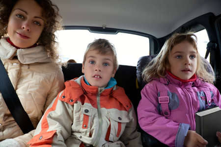 back seat: Mother with son and daughter sit on back seat of car