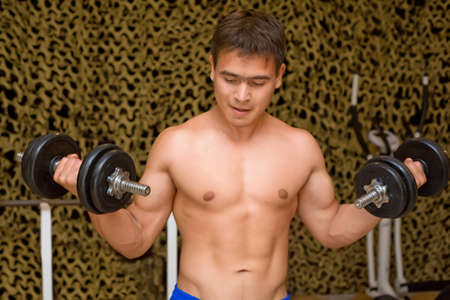 strong bodybuilder training muscles in gym, training bicepses photo