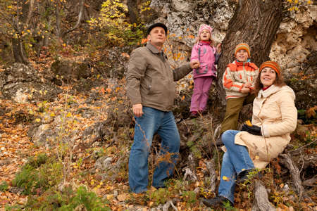 Mother, daughter, son and grandfather in autumnal forest near the tree  Stock Photo - 9123181