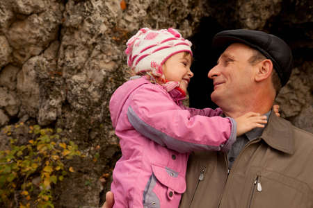 Grandfather hold granddaughter in his nahds near the stone wall Stock Photo - 9123180