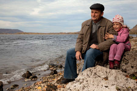 grand daughter: The grandfather and grand daughter sit on the stone near the lake