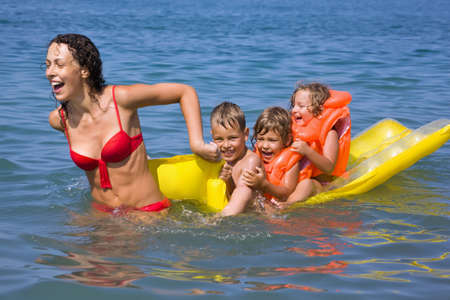 underwater woman: young woman rolls three children on an inflatable mattress in sea Stock Photo