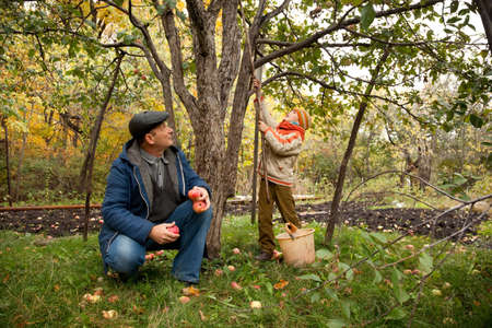 sons and grandsons: Grandson and grandfather neat the apple tree in autumnal garden