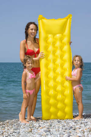 small group of objects: young woman and two little girls standing on beach, having control over an inflatable mattress