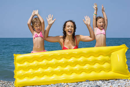 lifted hands: young woman and two little girls standing behind an inflatable mattress on beach, lifted hands upwards